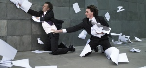 Two businessmen kneeling on pavement, reaching for paper blowing in wind